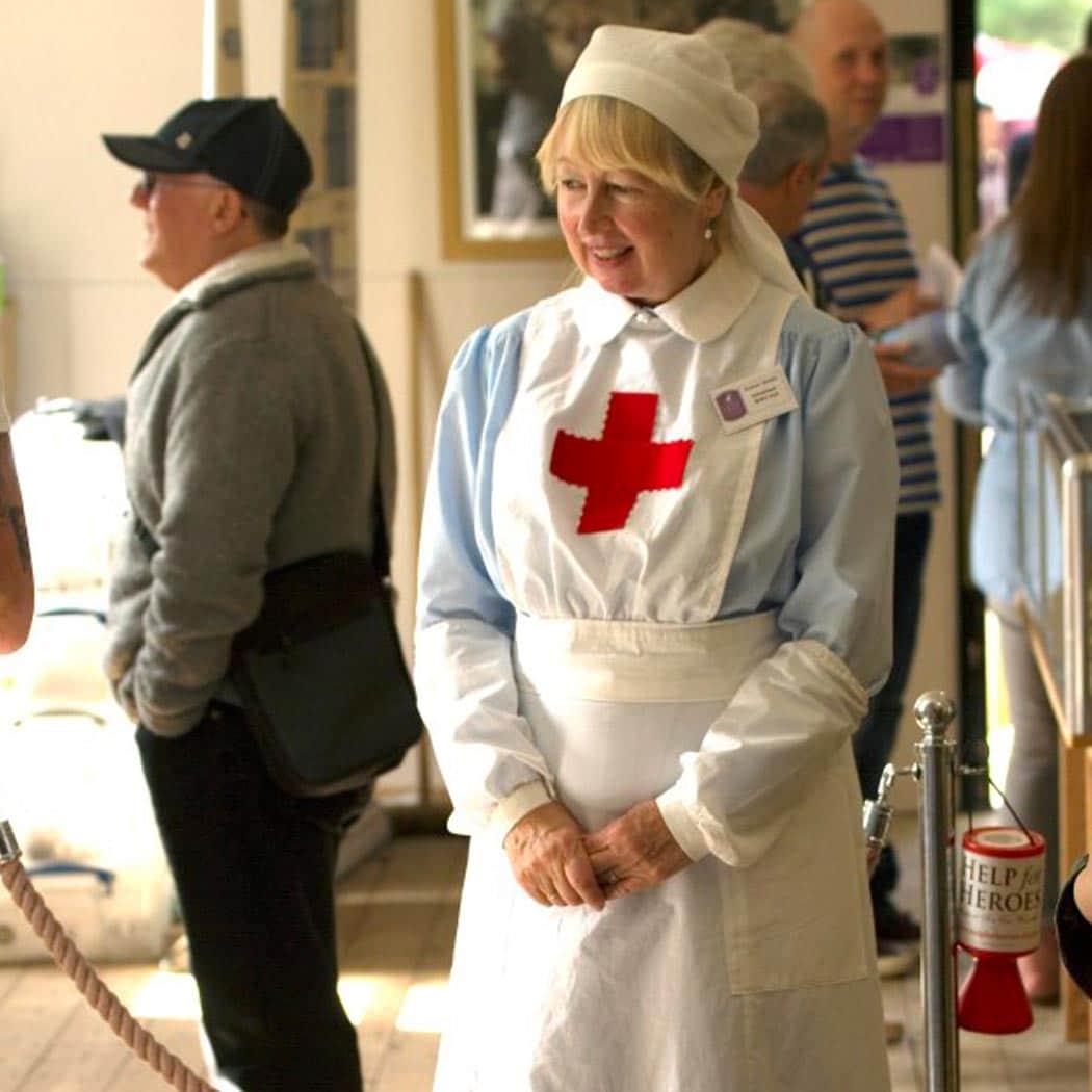 lady dressed in british red cross uniform.