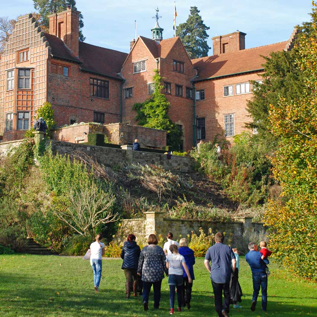 large red bricked house in foreground with extended family walking up to it.