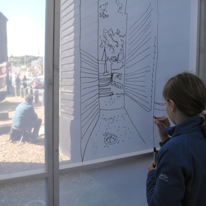 Young girl drawing a picture on a transparent material, with beach huts outside.