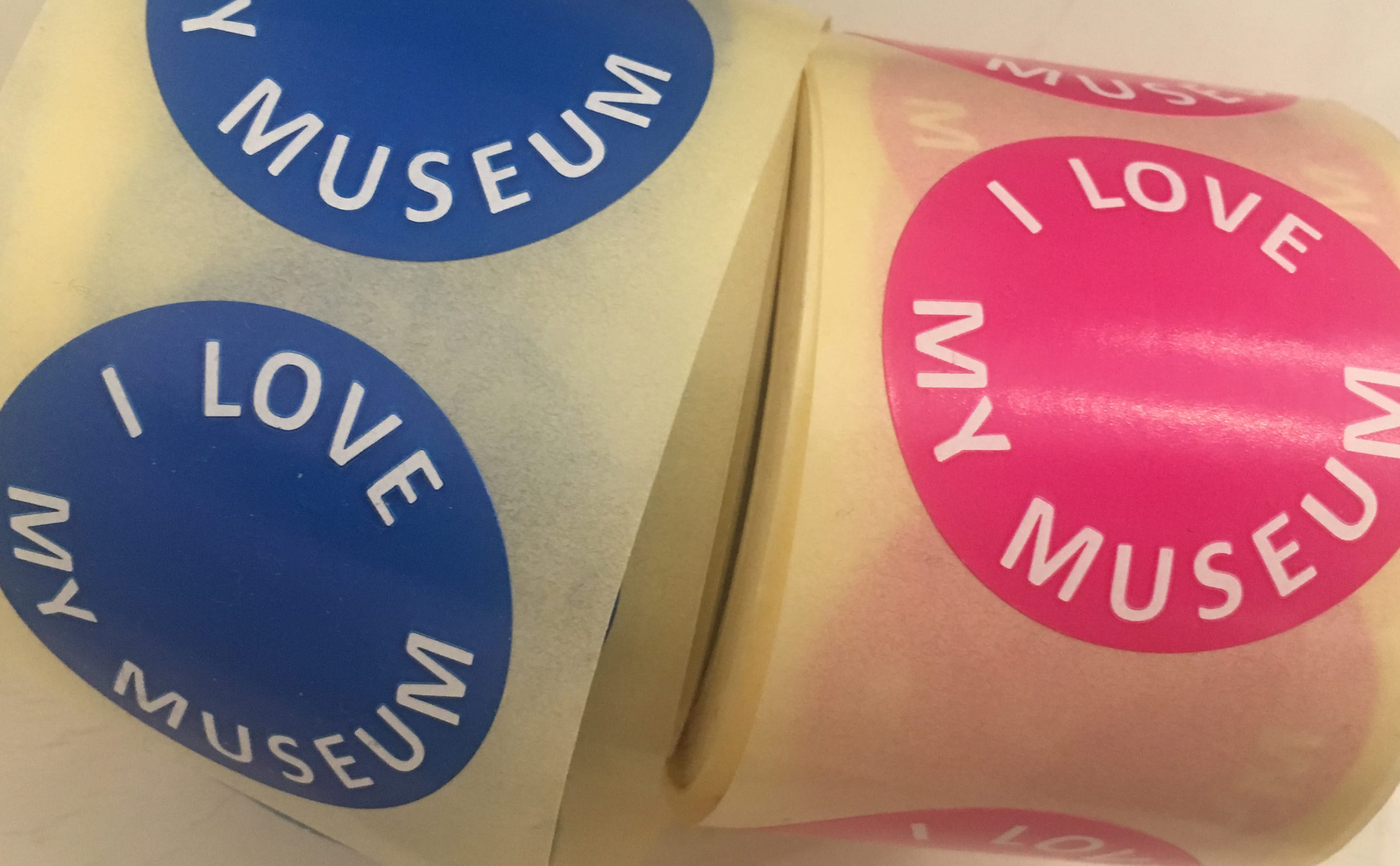 Two rolls of stickers, one blue, one pick, saying I Love my Museum.