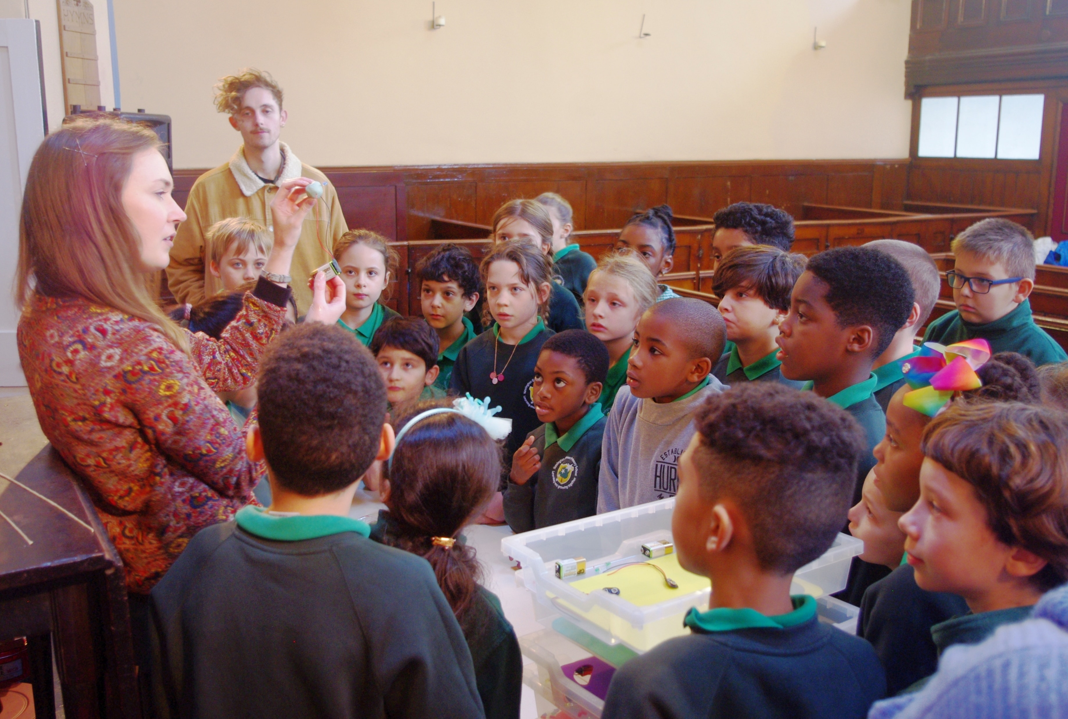 Woman talking to a group of school children.