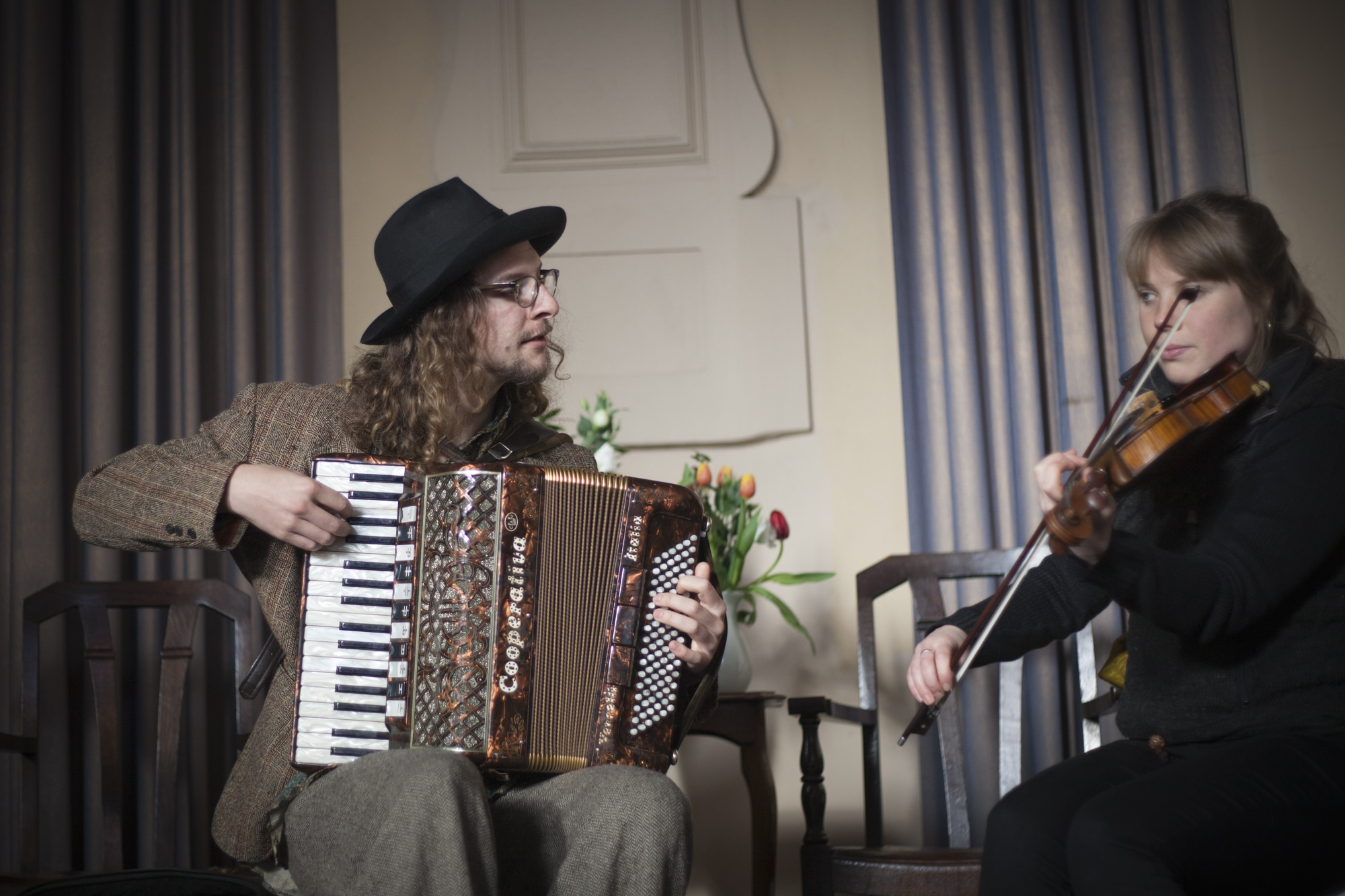 A man playing accordian and a woman playing the violin.