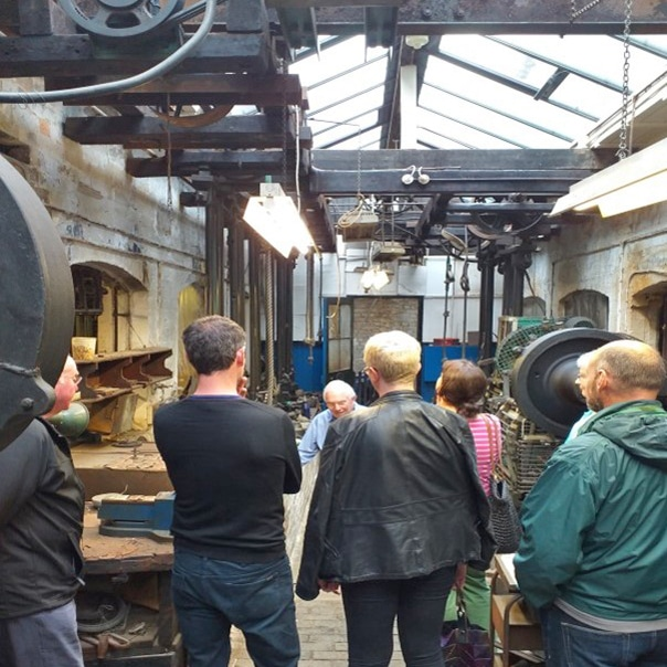 A group of people stand in an old industrial workshop, watching a man showing them something.